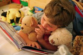 reading book boy and stuffed animals
