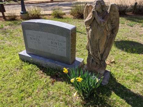 graveyard with yellow daffodils angel and tombstone